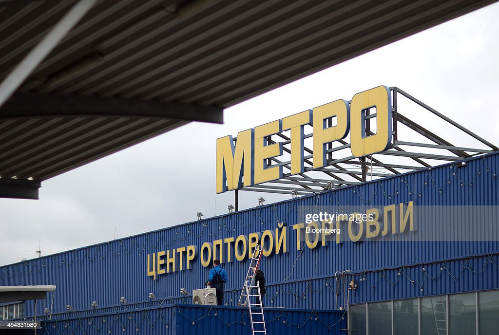 Maintenance workers carry ladders onto the roof of a Metro Cash & Carry store, the Russia unit of Metro AG, in Moscow, Russia, on Friday, Aug. 29, 2014. Metro Cash & Carry has warned that domestic food suppliers are trying to increase some food prices as local produce is substituted for EU, Norwegian and U.S. equivalents which have been sanctioned. Photographer: Andrey Rudakov/Bloomberg via Getty Images