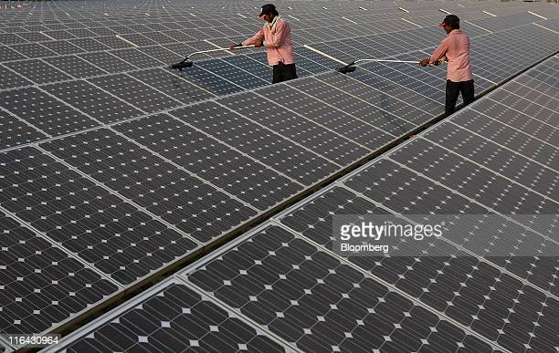 Maintenance workers clean solar panels manufactured by Tata BP Solar India Ltd at North Delhi Power Ltd's Keshavpuram power station in New Delhi...