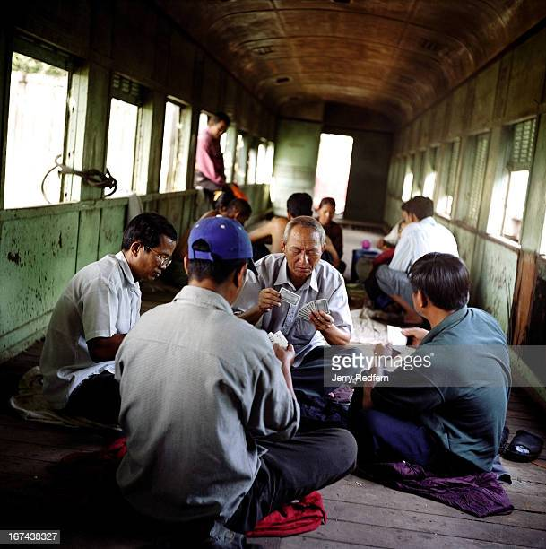 Maintenance workers for the Cambodian railway system play cards in an abandoned car in the Phnom Penh rail yards The system has no new rolling stock...