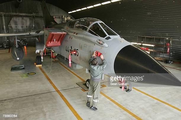 Maintenance workers secure a German Luftwaffe Tornado jet fighter at the Schleswig Jagel Luftwaffe base on March 13 2007 in Jagel Germany Six...