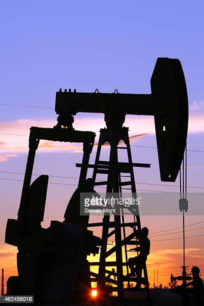 Maintenance workers work on a CNPC 'nodding donkey' oil pump at sunset in an oilfield on July 13 2006 in Daqing Heilongjiang province China China...
