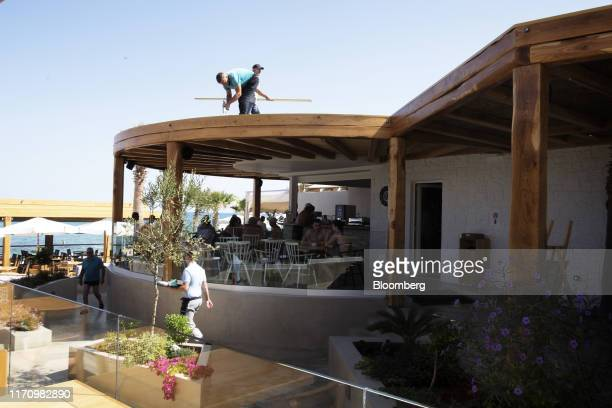 Maintenance workers work on the roof of a beach bar opposite Cactus Hotel in Hersonissos, on the island of Crete, in Greece, on Tuesday, Sept. 24,...