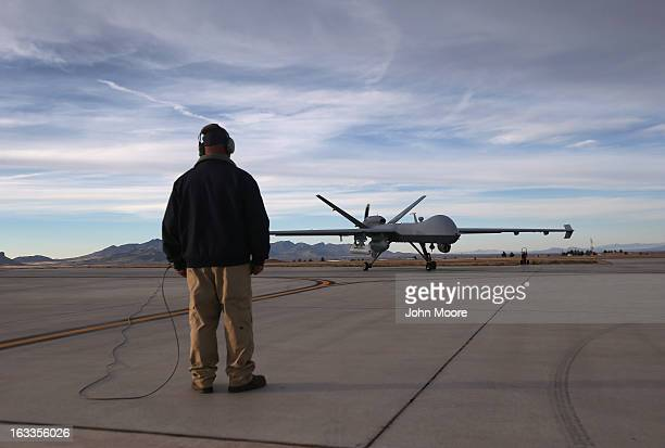 Maintenence personel watch as a Predator drone operated by US Office of Air and Marine taxis to the tarmac for a fight over southern Arizona near the...