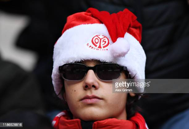 Mainz 05 fan wearing a Christmas hat watches the action during the Bundesliga match between 1. FSV Mainz 05 and 1. FC Union Berlin at Opel Arena on...