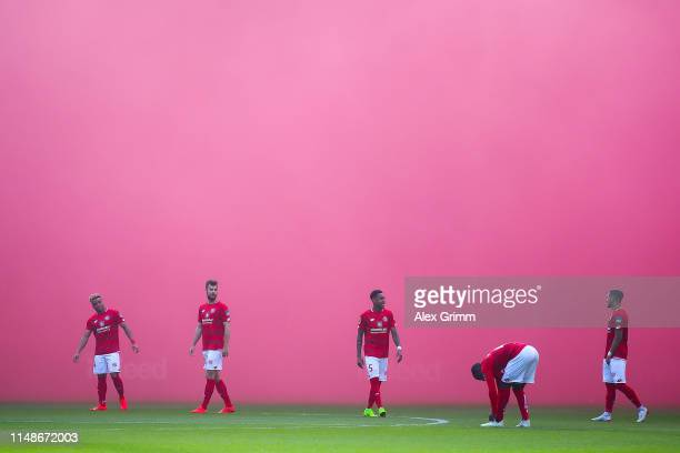 Mainz 05 players wait on the pitch as purple smoke from flares fill the air during the Bundesliga match between Eintracht Frankfurt and 1 FSV Mainz...