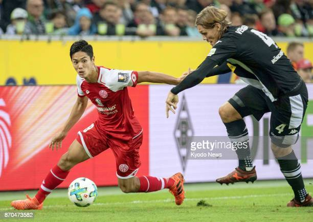 FSV Mainz 05 striker Yoshinori Muto and Borussia Moenchengladbach defender Jannik Vestergaard vie for the ball during the first half of a Bundesliga...