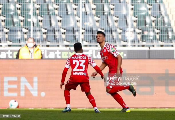 Mainz' Austrian forward Karim Onisiwo celebrates scoring the opening goal with Mainz' Austrian defender Philipp Mwene during the German first...