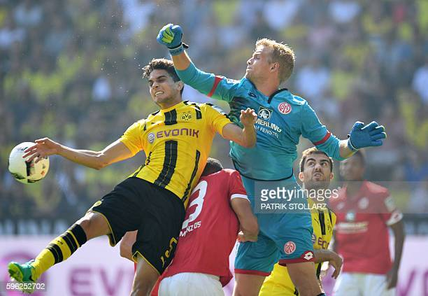 Mainz' Danish goalkeeper Jonas Loessl Mainz' Nigerian defender Leon Balogun and Dortmund's Spanish defender Marc Bartra vie for the ball during the...