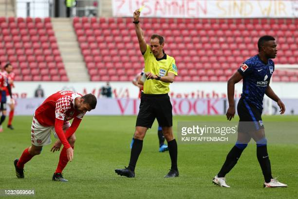 Mainz' German defender Stefan Bell receives a yellow card from the referee as Hertha Berlin's Colombian forward Jhon Cordoba walks away during the...
