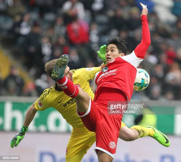 Mainz' Japanese forward Yoshinori Muto and Frankfurt's Finnish goalkeeper Lukas Hradecky vie for the ball during the German first division Bundesliga...