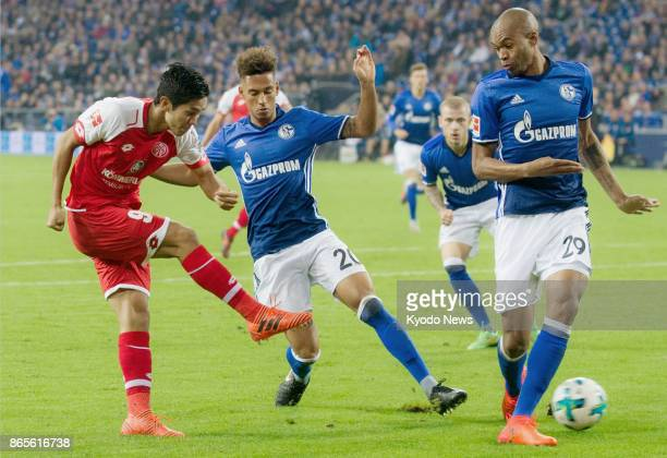 Mainz striker Yoshinori Muto kicks the ball past Thilo Kehper and Naldo of Schalke during the second half of their German Bundesliga match at Veltins...