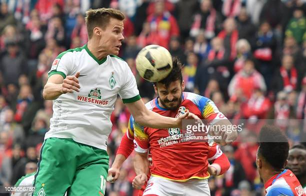 Mainz's Giulio Donati and Bremen's Niklas Moisander vie for the ball in the German Bundesliga soccer match between FSV Mainz and Werder Bremen in the...