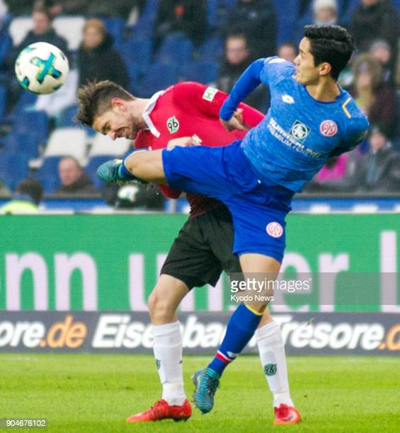 Mainz's Japan international forward Yoshinori Muto battles for the ball in the first half of his side's 32 defeat by Hanover in a Bundesliga match in...