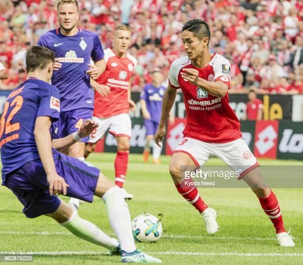 Mainz's Yoshinori Muto tries to break away from Werder Bremen's Marco Friedl during a match in Mainz Germany on May 12 2018 Werder Bremen won 21...