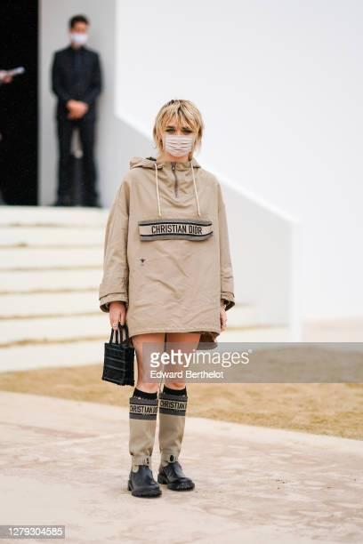 Maisie WIlliams wears a beige poncho/coat, a Dior bag, high beige boots, outside Dior, during Paris Fashion Week - Womenswear Spring Summer 2021 on...