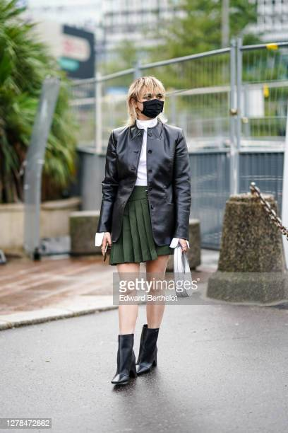 Maisie Williams wears a black protective face mask, a white top, a black leather jacket, a green pleated skirt, black leather pointy boots, outside...