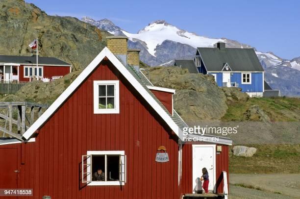Maisons traditionnelles colorees devant les montagnes de Polhems Fjold Region d'Ammassalik