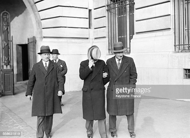 Maitre Gaulier avocat d'Arlette Stavisky sortant le visage cache du bureau du juge d'instruction a Paris France le 28 mars 1934