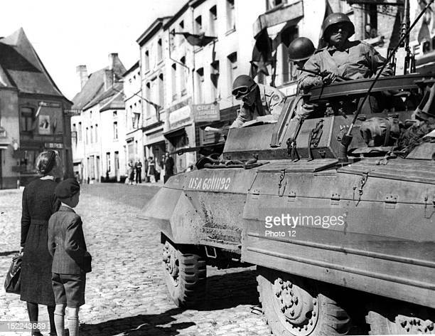 Maj Gen J Lawton Collins C G of an US Corps checks his maps in an armored vehicle in Beaumont while a Belgian mother and son gaze silently at the...