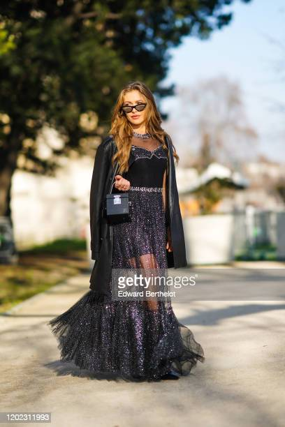 Maja Malnar wears sunglasses, a black cube bag, a black leather jacket, a black lace mesh glitter dress with a pleated part, outside Elie Saab,...