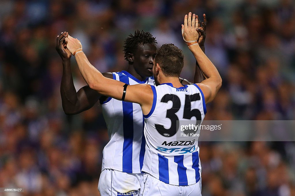 Majak Daw and Aaron Black of the Kangaroos celebrate a goal during the round six AFL match between the Fremantle Dockers and the North Melbourne Kangaroos at Patersons Stadium on April 25, 2014 in Perth, Australia.