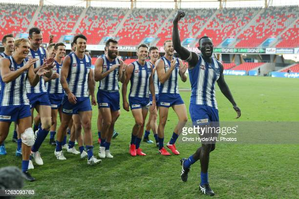 Majak Daw and the Kangaroos celebrates winning the round nine AFL match between North Melbourne Kangaroos and the Adelaide Crows at Metricon Stadium...