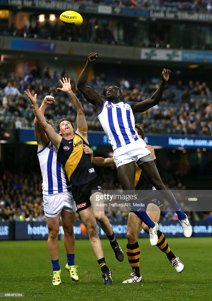 Majak Daw of the Kangaroos and Dylan Grimes of the Tigers compete for the ball during the 2015 AFL round 23 match between the Richmond Tigers and the North Melbourne Kangaroos at Etihad Stadium, Melbourne, Australia on September 4, 2015.