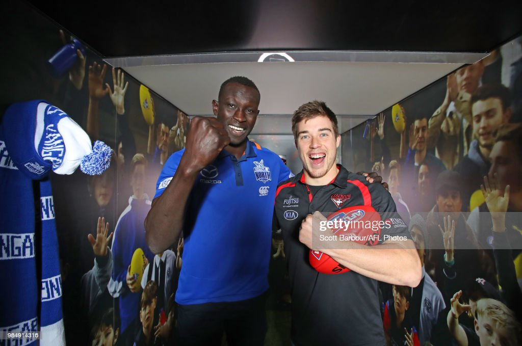 Majak Daw of the Kangaroos and Zach Merrett of the Bombers pose inside of the the Scream-a-Meter during the Simply Energy AFL and Etihad Stadium Announcement at Etihad Stadium on June 26, 2018.