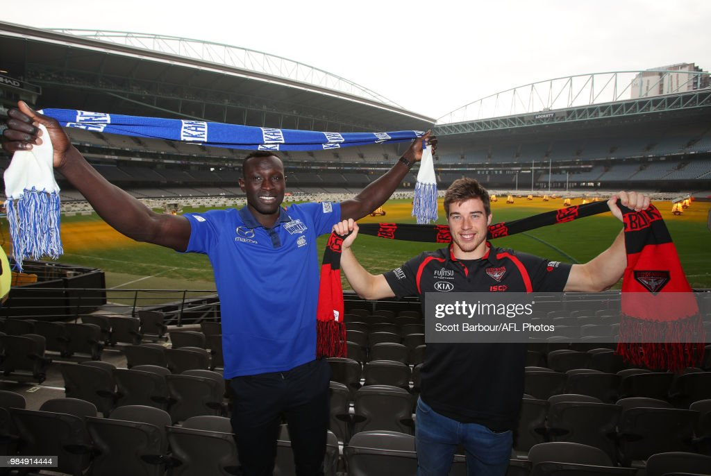 Majak Daw of the Kangaroos and Zach Merrett of the Bombers pose with the Simply Energy Mascots during the Simply Energy AFL and Etihad Stadium Announcement at Etihad Stadium on June 26, 2018.