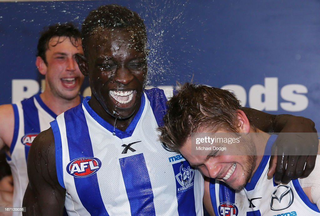 Majak Daw (C) of the Kangaroos celebrates the win with Taylor Hine during the round four AFL match between the North Melbourne Kangaroos and the Brisbane Lions at Etihad Stadium on April 21, 2013 in Melbourne, Australia.