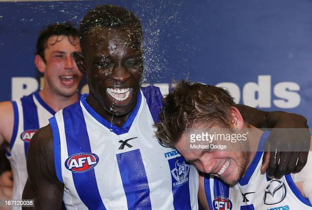 Majak Daw of the Kangaroos celebrates the win with Taylor Hine during the round four AFL match between the North Melbourne Kangaroos and the Brisbane...