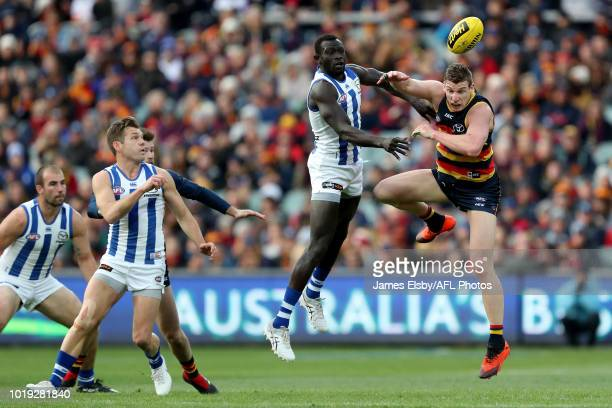 Majak Daw of the Kangaroos clashes with Josh Jenkins of the Crows during the 2018 AFL round 22 match between the Adelaide Crows and the North...