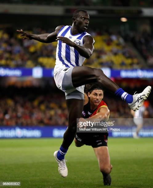 Majak Daw of the Kangaroos kicks the ball during the 2018 AFL round15 match between the Essendon Bombers and the North Melbourne Kangaroos at Etihad...