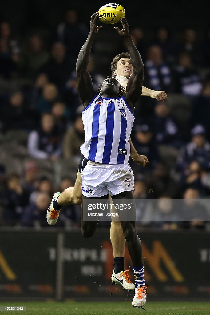 Majak Daw of the Kangaroos marks the ball against Michael Jamison of the Blues during the round 18 AFL match between the Carlton Blues and the North Melbourne Kangaroos at Etihad Stadium on July 18, 2014 in Melbourne, Australia.
