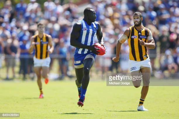 Majak Daw of the Kangaroos runs with the ball away from Josh Gibson of the Hawksduring the JLT Community Series AFL match between the North Melbourne...