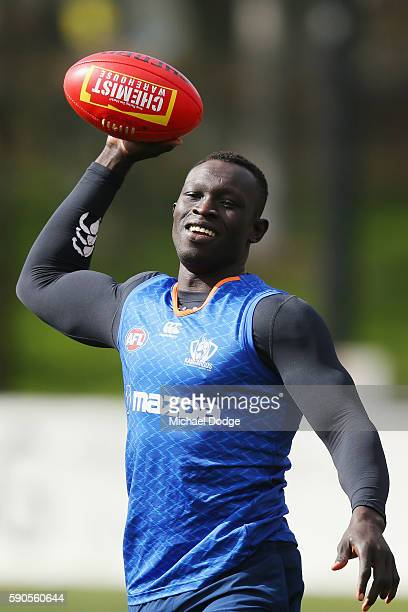 Majak Daw of the Kangaroos throws a ball gridiron style during a North Melbourne Kangaroos AFL training session at Arden Street Ground on August 17,...