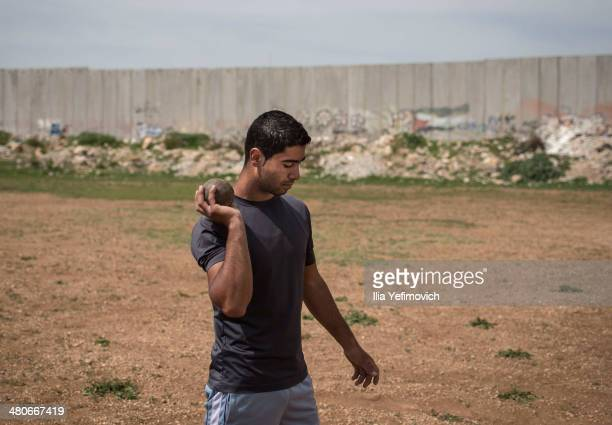 Majd Qunees a student at Al Quds University sports department seen holding a metal ball during a practise at Al Quds University on March 24 2014 in...