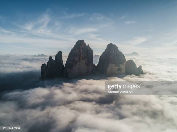 majestic aerial shot above the clouds looking towards tre cime di lavaredo, italy - felsformation stock-fotos und bilder