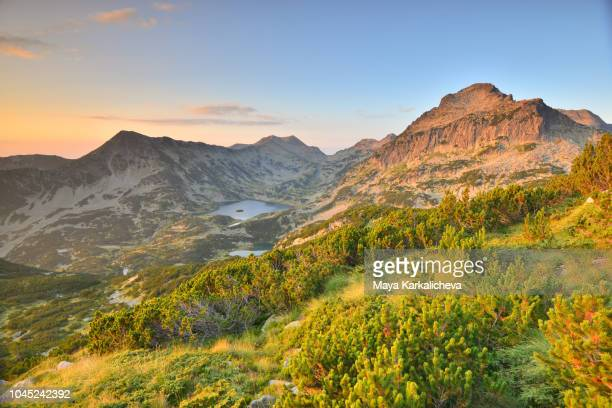 majestic alpenglow on a mountain peak with view of beautiful valley with glacial lake - bansko stock pictures, royalty-free photos & images