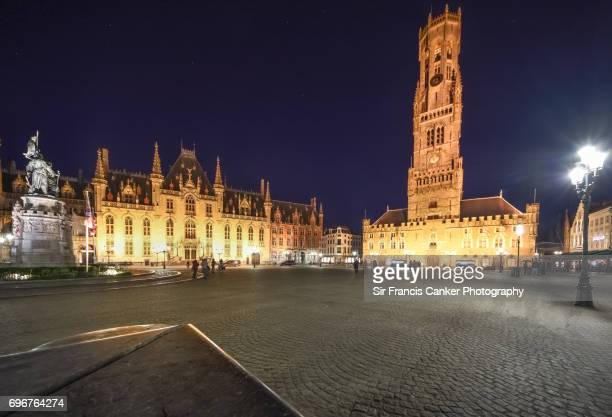 Majestic Belfry of Bruges on Grote Market square (Grand Place) illuminated at night in Flanders, Belgium