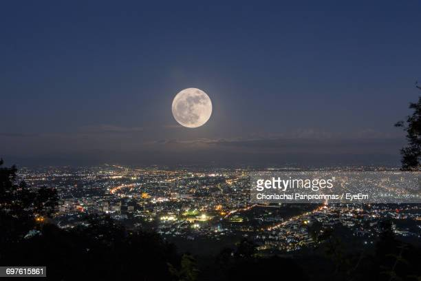 majestic full moon over illuminated city against sky - pleine lune photos et images de collection