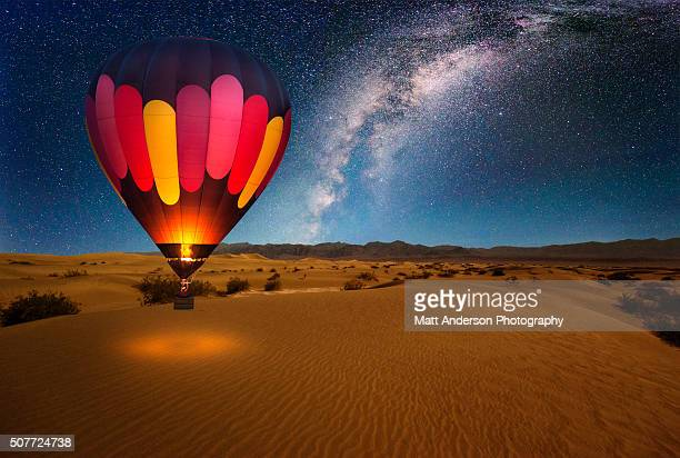 a majestic hot air balloon soars under the stars of the milky way, over the desert - mesquite dunes of death valley national park. moonlight provides luminosity showing the patterns and shapes of the desert landscape. - balloon ride stock pictures, royalty-free photos & images