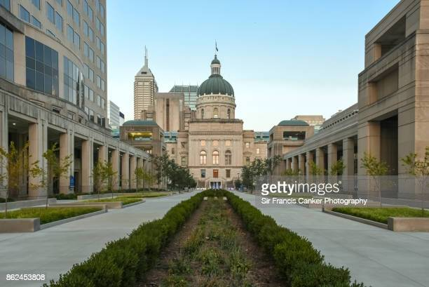 majestic indiana state capitol facade at dusk with skyscrapers on background in indianapolis, indiana, usa - indiana stock-fotos und bilder