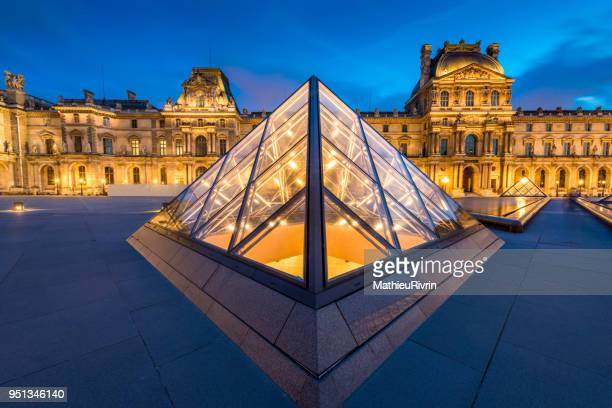 majestic louvre museum - louvre pyramid stock photos and pictures