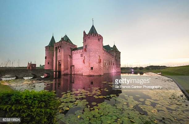 Majestic moated 'Muiderslot' castle reflected on waters at sunset in Muiden, the Netherlands