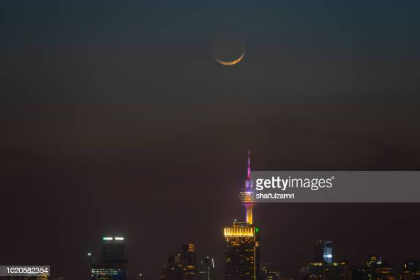 majestic moon rise over kl tower and surrounded buildings in downtown kuala lumpur, malaysia. - shaifulzamri stock-fotos und bilder