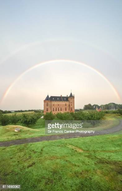 Majestic Muiderslot castle under a perfect double rainbow in Muiden, Amsterdam, Netherlands