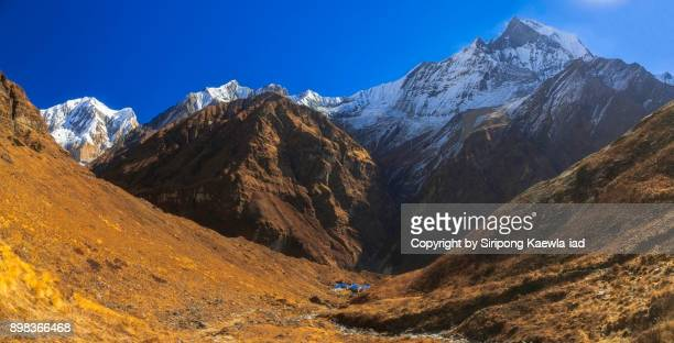 majestic panoramic view of the annapurna mountain range and the peak of machhapuchhre from the machhapuchhre base campe (mbc) in the dry season. - copyright by siripong kaewla iad stock photos and pictures