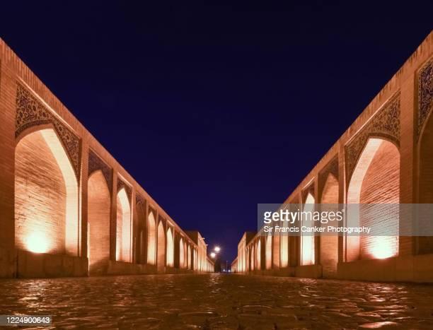 majestic pol-e khaju bridge over zayandeh river illuminated at night in isfahan, iran - ハージュ橋 ストックフォトと画像