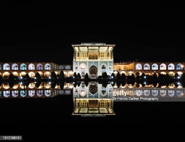 "majestic reflection of ""kakh-e ali qapu"" palace (""ali qapu palace"") illuminated at night on imam square's (""naqsh-e jahan imam square"") reflecting pool in isfahan, iran - isfahan stad stockfoto's en -beelden"